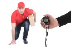 Delivery boy in a rush delivering a package isolated against white background Stock Photos