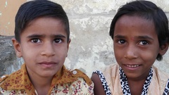 Indian kids, one girl and one boy, seated together and talking  Stock Footage