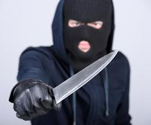 Masked man aims with knife. on gray background Stock Photos