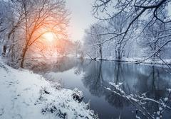 Colorful landscape with snowy trees, beautiful frozen river at sunset Stock Photos