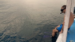 Man jumping off boat and preparing for snorkeling in sea, super slow motion  Stock Footage