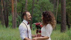 Beautiful young couple in Bohemian style fashion in the forest. Looking into Stock Footage