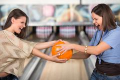 Two young women are pulling the bowling ball to each other. Stock Photos