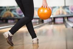 Young woman is playing bowling, preparing to throw ball. Stock Photos
