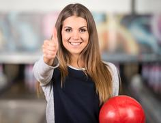 Beautiful young woman in a bowling alley is having fun. Stock Photos