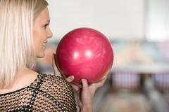 Portrait of beautiful young woman with a bowling ball in her hands, back view. Stock Photos