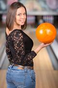 Young woman in a bowling alley is smiling and holding bowling ball. Stock Photos