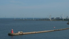 Rotating wind turbine in the sea at harbour Stock Footage