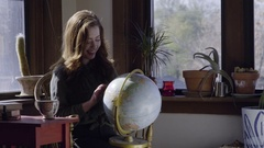 Young Woman Holds A Globe In Her Lap, Spins It, Dreams Of Travel Destinations Stock Footage