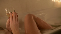 Woman holding a glass of white wine and take a bath Stock Footage