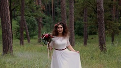 Beautiful bride in a vintage dress with colored bouquet in summer forest. Goes Stock Footage