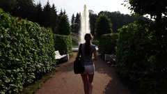 Woman walk to fountain through trimmed hedge alley, slow motion follow camera Stock Footage