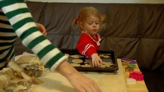 Woman and toddler girl preparing gingerbread for family Christmas eve dinner. Stock Footage