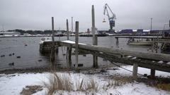 Old wooden jetty, fishing boats, snow and lead-gray water of Baltic Sea. Dolly. Stock Footage