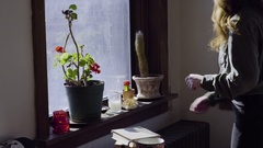 Young Woman Kneels Down And Lights A Candle In Windowsill, Then Exits Frame Stock Footage