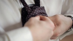 Groom ties a tie, close up, preparation for a wedding Stock Footage