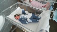Nurse dresses up a newly-born in a hospital ward Stock Footage