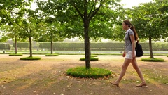 Young adult woman quickly go at formal garden, tracking shot Stock Footage