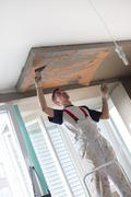 Plasterer renovating indoor walls and ceilings. Finishing works Stock Photos