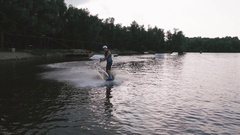 A man in a diving suit rides on the lake on a wakeboard Stock Footage