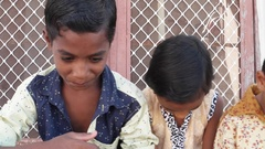 Indian kids with their heads down but still smiling smugly, handheld  Stock Footage