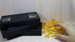 Stack of VHS video tape cassette and potato chips Stock Footage