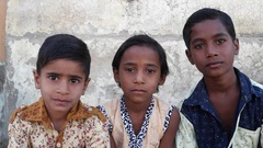 Three Indian kids sitting and looking at the camera and speaking Stock Footage