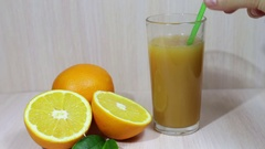 Orange juice in a glass and fresh fruits on wooden background Stock Footage