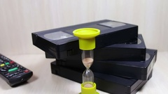 Stack of VHS video tape cassette and hourglass Stock Footage