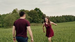 Happy couple in love have fun in the nature. Beautiful young woman jumps into Stock Footage