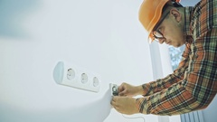 Builder with screwdriver fixing socket indoors Stock Footage