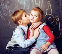Little cute boy kissing blonde girl in classroom at blackboard, first school Stock Photos