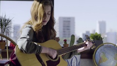 Happy Young Woman Playing Acoustic Guitar In Her City Apartment Stock Footage