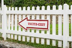 Arrow on picket fence indicating the exit. Stock Photos