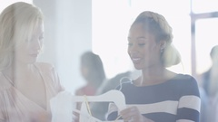 4K Pregnant woman shopping with a friend in fashionable boutique clothing store Stock Footage