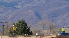 Roof top construction workers with hard hats on Stock Footage