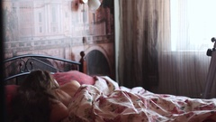 A girl wakes up in bed Stock Footage