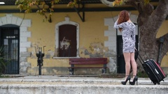 Slim woman front of a traditional train station pull a huge bag on wheels   Stock Footage
