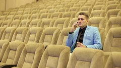 Elegant man talking on the phone in an empty concert hall. Stock Footage
