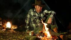 4K.Man   in cowboy hat  near  bonfire goes sleep.  Travel life.  Arkistovideo
