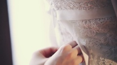 Woman tie ribbons on back side of lacy wedding dress to bride. Celebration day Stock Footage
