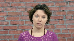 Adult woman with short hair depict dispraise in camera. Casting. Brick wall Stock Footage