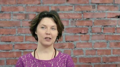 Adult woman tell something to man behind camera. Casting. Brick wall. Waggle Stock Footage