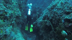 Divers swim underwater with aqualungs between reefs. Sealife. Deepness. Bubbles Stock Footage