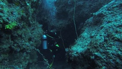 Divers swim underwater with aqualungs between reefs. Blue water. Deepness. Coral Stock Footage
