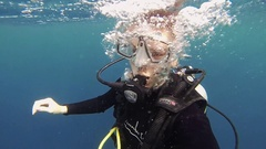 Diver girl underwater with aqualung. Surfacing from depth. Scubadiving. Ocean Stock Footage