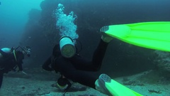 Divers swim underwater with aqualungs. Deepness. Reef. Flippers. Scubadiving Stock Footage
