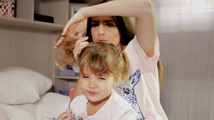 Happy young mother making pigtails to little daughter Stock Footage