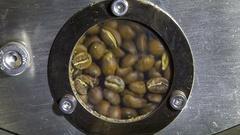 Coffee beans roasting in roaster; window view Stock Footage