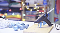 Glue gun and Christmas baubles decor on white table 4K Stock Footage